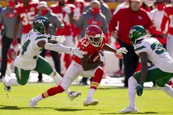 Kansas City Chiefs wide receiver Byron Pringle (13) runs for a first down after catching a pass as New York Jets cornerback Brian Poole (34) and Pierre Desir (35) combine to make the stop in the first half of an NFL football game on Sunday, Nov. 1, 2020, in Kansas City, Mo. (AP Photo/Charlie Riedel)