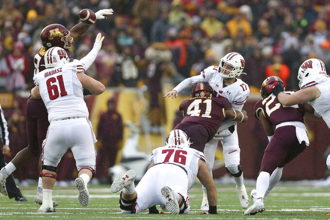 Wisconsin quarterback Jack Coan (17) throws the ball before getting hit by Minnesota linebacker Thomas Barber (41) during an NCAA college football game Saturday, Nov. 30, 2019, in Minneapolis. (AP Photo/Stacy Bengs)
