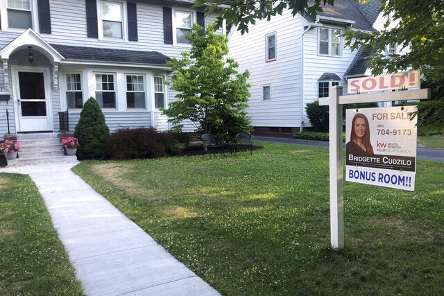 FILE - In this July 4, 2020 file photo, a sold sign hangs in front of a house in Brighton, N.Y.  U.S. average rates on long-term mortgages fell this week, pushing the key 30-year loan to a record low for the eighth time this year.   (AP Photo/Ted Shaffrey, File)