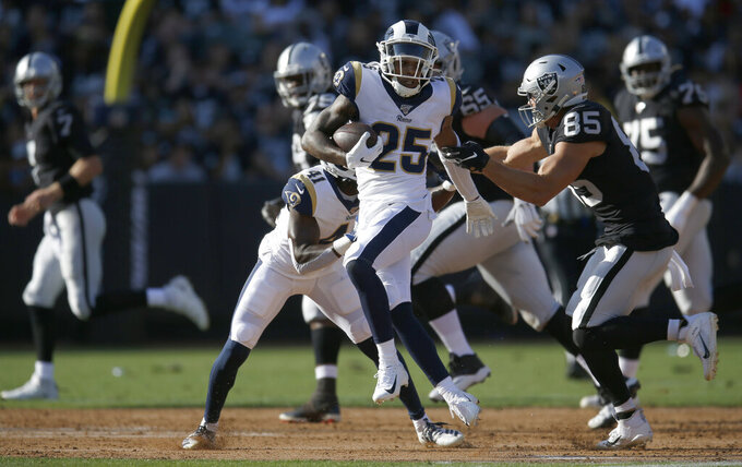 Los Angeles Rams' Kevin Peterson (25) slips the grip of Oakland Raiders' Derek Carrier (85) after intercepting a pass from Mike Glennon, left, during the first half of a preseason NFL football game Saturday, Aug. 10, 2019, in Oakland, Calif. (AP Photo/D. Ross Cameron)