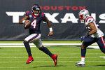 Houston Texans quarterback Deshaun Watson (4) runs past New England Patriots linebacker Josh Uche (53) during the first half of an NFL football game, Sunday, Nov. 22, 2020, in Houston. (AP Photo/David J. Phillip)