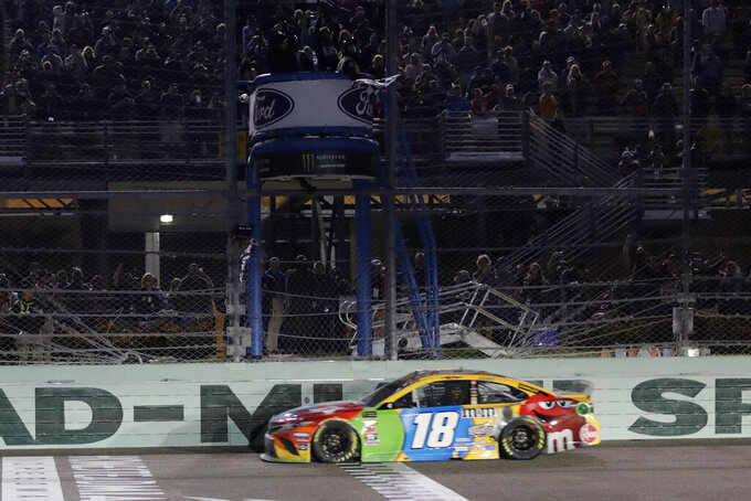 Kyle Busch crosses the finish line to win a NASCAR Cup Series auto racing season championship at Homestead-Miami Speedway in Homestead, Fla., Sunday, Nov. 17, 2019.(AP Photo/Luis M. Alvarez)
