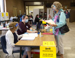 Sally Lambert checks into the polls to vote in the Republican primaries, on Tuesday, June 23, 2020 at Hidden Valley Middle School, in Roanoke, hosted in the cafeteria, with the help of Shirley Prillaman, left, and Lenie DeFrancesco. (Stephanie Klein-Davis/The Roanoke Times via AP)