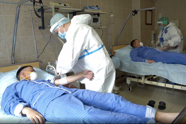 In this photo made from footage provided by the Russian Defense Ministry on Wednesday, July 15, 2020, medical workers in protective gear prepare to draw blood from volunteers participating in a trial of a coronavirus vaccine at the Budenko Main Military Hospital outside Moscow, Russia. Russia is boasting that it's about to be the first country to approve a COVID-19 vaccine, but scientists worldwide are sounding the alarm that the headlong rush could backfire. (Russian Defense Ministry Press Service via AP)