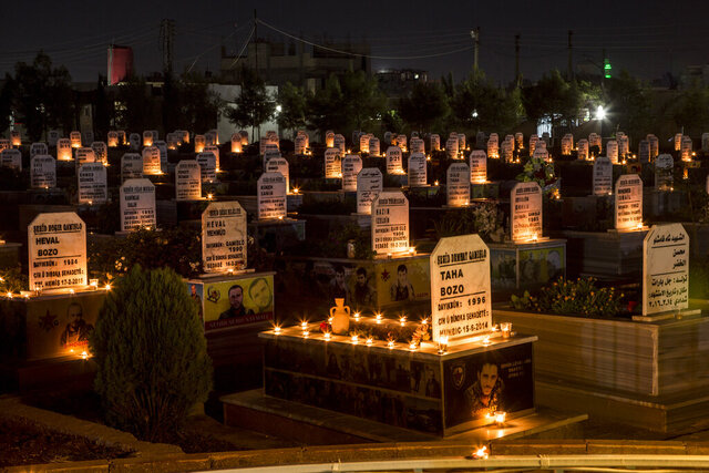 FILE - In this Oct. 31, 2019 file photo, candles are lit on the graves of people killed during Syrian war, in the town of Qamishli, north Syria. Investigators for the U.N.-backed Human Rights Council said on Monday, March 2, 2020, that they had found evidence of war crimes in Syria committed by nearly all sides in the conflict during the second half of last year and into January. (AP Photo/Baderkhan Ahmad, File)
