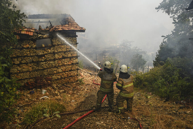 Firefighters water to stop a fire in the fire-devastating Sirtkoy village, near Manavgat, Antalya, Turkey, Sunday, Aug. 1, 2021. More than 100 wildfires have been brought under control in Turkey, according to officials. The forestry minister tweeted that five fires are continuing in the tourist destinations of Antalya and Mugla. (AP Photo)