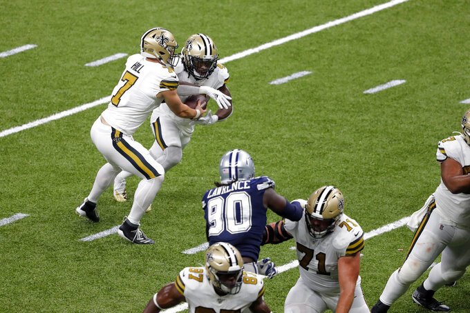 New Orleans Saints quarterback Taysom Hill (7) phands off to running back Alvin Kamara in the second half of an NFL football game against the Dallas Cowboys in New Orleans, Sunday, Sept. 29, 2019. (AP Photo/Bill Feig)