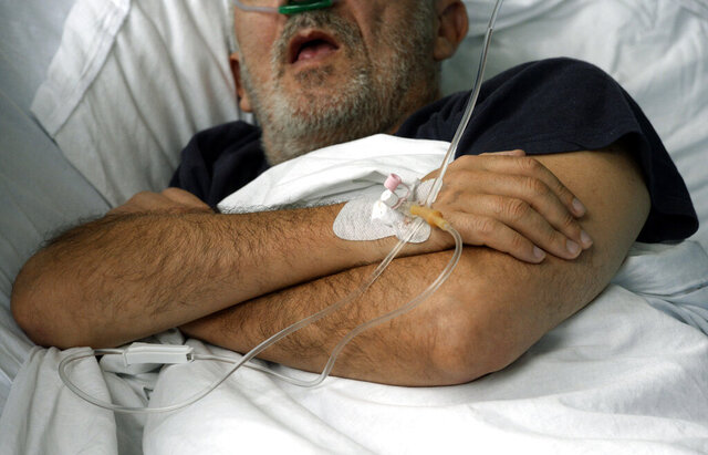 A patient on oxygen support is seen in the COVID-19 ward at a former military hospital in the capital Sarajevo, Bosnia, Thursday, Nov. 19, 2020. Doctors in Bosnia, one of the hardest hit countries in the Balkans with the new coronavirus, are appealing on the citizens to respect preventive measures and help the ailing health system. (AP Photo/Kemal Softic)