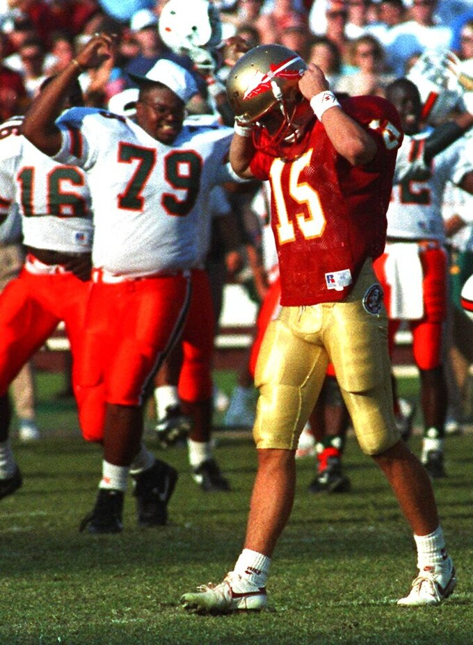FILE - In this Nov. 16, 1991, file photo, Miami's Jesse Mitchell (79) exults as dejected Florida State kicker Gerry Thomas (15) walks off the field after missing a field goal that would have won the game for FSU in Tallahassee, Fla. The game was the first 1-2 matchup between two teams in the same state since Purdue and Notre Dame did in 1968, and it marked a shift in the landscape of college football to the Sunshine State. (AP Photo/Don Dughi, File)