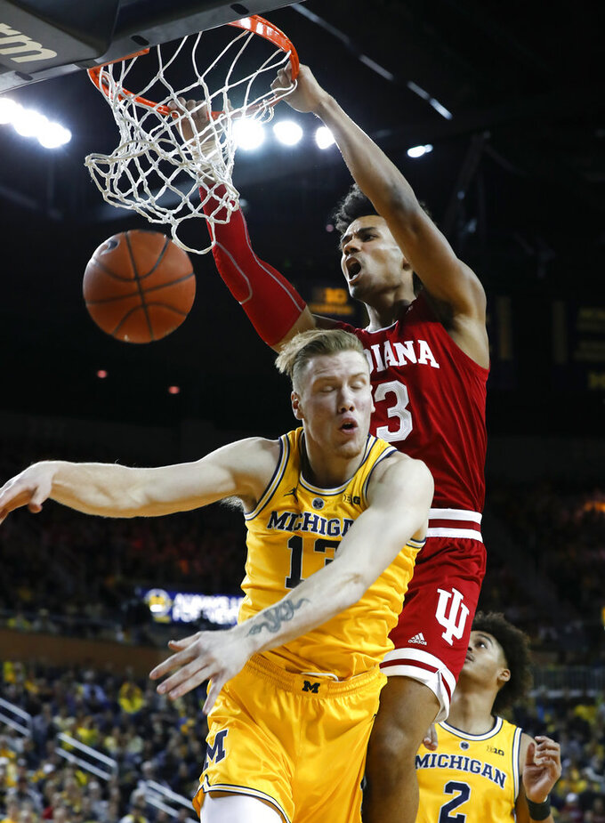 Indiana forward Justin Smith (3) dunks on Michigan forward Ignas Brazdeikis (13) in the first half of an NCAA college basketball game in Ann Arbor, Mich., Sunday, Jan. 6, 2019. (AP Photo/Paul Sancya)