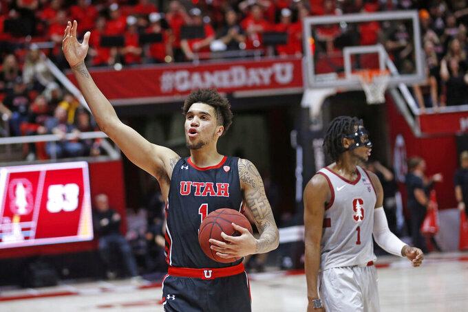 Utah forward Timmy Allen (1) celebrates as Stanford guard Daejon Davis (1) looks away in overtime of an NCAA college basketball game Thursday, Feb. 6, 2020, in Salt Lake City. Utah won 64-56. (AP Photo/Rick Bowmer)