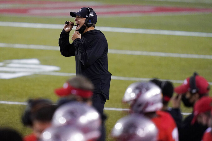 New Mexico head coach Danny Gonzales speaks with players during the second half of an NCAA college football game against Nevada, Saturday, Nov. 14, 2020, in Las Vegas. (AP Photo/John Locher)