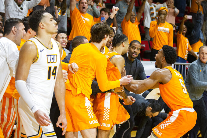 Tennessee players swarm guard Lamonte Turner (1) after hitting the winning shot at the buzzer as his defender, Virginia Commonwealth forward Marcus Santos-Silva (14), walks off the court in the Emerald Coast Classic in Niceville, Fla., Saturday, Nov. 30, 2019. Tennessee defeated Virginia Commonwealth 72-69. (AP Photo/Mark Wallheiser)