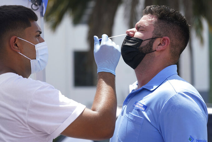 EMS technician Emmanuel Orrego, left, administers the COVID-19 PCR test to Yosdany Lugo, Monday, July 26, 2021, in Miami. Florida accounted for a fifth of the nation's new infections last week, more than any other state, according to the CDC. (AP Photo/Marta Lavandier)