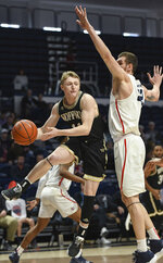 Wofford guard Ryan Larson (11) passes the ball around Samford center Ruben Guerrero (32) during the first half of an NCAA college basketball game Saturday, March 2, 2019, in Birmingham, Ala. (AP Photo/Julie Bennett)