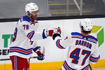 New York Rangers defenseman K'Andre Miller (79) is congratulated by Morgan Barron (47) after his goal during the second period of an NHL hockey game against the Boston Bruins, Saturday, May 8, 2021, in Boston. (AP Photo/Charles Krupa)