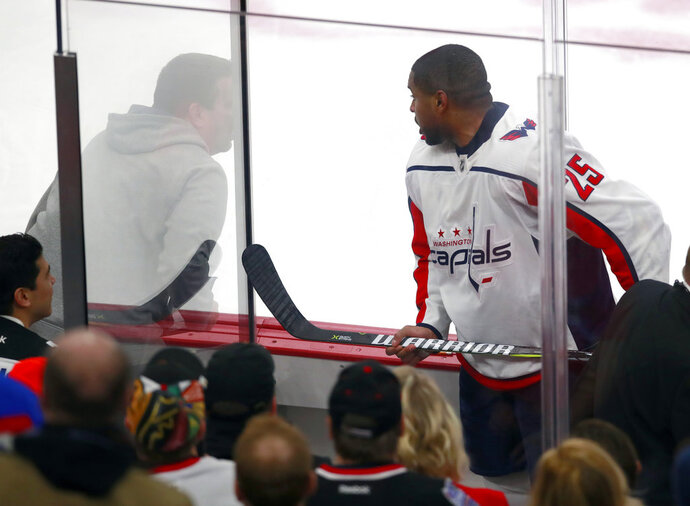 "FILE - In this Feb. 17, 2018, file photo, Washington Capitals right wing Devante Smith-Pelly (25) argues from the penalty box with Chicago Blackhawks fans during the third period of an NHL hockey game in Chicago. Washington Capitals forward heard the unmistakably racial taunts from fans from inside the penalty box. As a black hockey player, he knew exactly what they meant by yelling, ""Basketball, basketball, basketball."" (AP Photo/Jeff Haynes, File)"