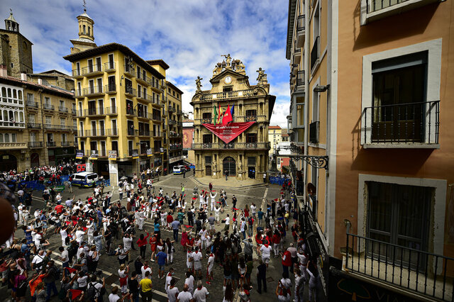 Residents, wearing white clothes and traditional red scarves, take to the streets on the day the ''txupinazo'' would usually take place to start the famous San Fermin festival, which was due canceled this year by the conoravirus, in Pamplona, northern Spain, Monday, July 6, 2020. (AP Photo/Alvaro Barrientos)