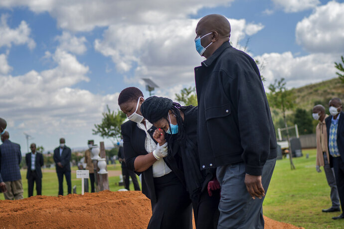 FILE - In this Sunday, April 12, 2020 file photo, relatives grieve for Benedict Somi Vilakasi, a Soweto coffee shop manager who died of a COVID-19 infection in a Johannesburg hospital, at his burial ceremony at the Nasrec Memorial Park outside Johannesburg, South Africa Thursday, April 16, 2020. Africa's coronavirus cases have surpassed 100,000, the Africa Centers for Disease Control and Prevention said Friday, May 22, 2020 as the continent with many fragile health systems has not yet seen the high numbers of other parts of the world. (AP Photo/Jerome Delay, File)