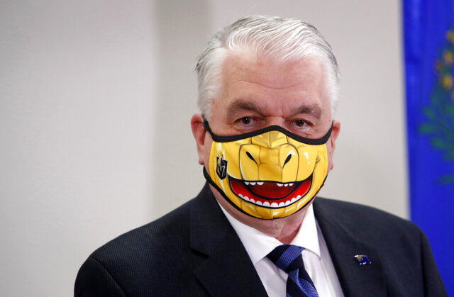 FILE - In this Sept. 29, 2020, file photo, Nevada Gov. Steve Sisolak speaks wearing a face mask themed after the Vegas Golden Knights' mascot Chance the Golden Gila Monster during a news conference in Las Vegas. Trick-or-treating has been canceled this year at the Nevada governor's mansion due to the coronavirus pandemic, and state health officials are advising people marking Halloween and El Día de los Muertos to avoid large gatherings. Sisolak said Wednesday, Oct. 14, 2020, the mansion will be decorated but the annual festivities will not take place to keep staff and visitors safe. (Steve Marcus/Las Vegas Sun via AP, Pool, File)