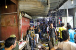 People and security forces gather at the site of a bombing in Wahailat market in Sadr City, Iraq, Monday, July 19, 2021. A roadside bomb attack targeted a Baghdad suburb Monday, killing at least 18 people and wounding dozens of others at a crowded market, Iraqi security officials said. (AP Photo/Khalid Mohammed)