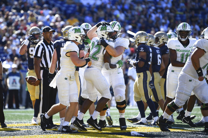 Marshall running back Rasheen Ali (22) is greeted by teammates after scoring his second touchdown of the first half against Navy during an NCAA college football game, Saturday, Sept. 4, 2021, Annapolis, Md. (AP Photo/Terrance Williams)