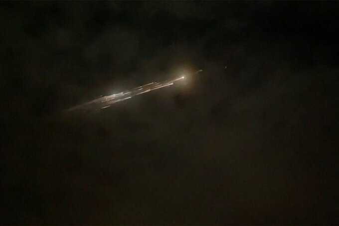 In this image taken from video provided by Roman Puzhlyakov, debris from a SpaceX rocket lights up the sky behind clouds over Vancouver, Wash. Thursday evening, March 25, 2021. The remnants of the second stage of the Falcon 9 rocket left comet-like trails as they burned up upon re-entry in the Earth's atmosphere according to a tweet from the National Weather Service. (Roman Puzhlyakov via AP)
