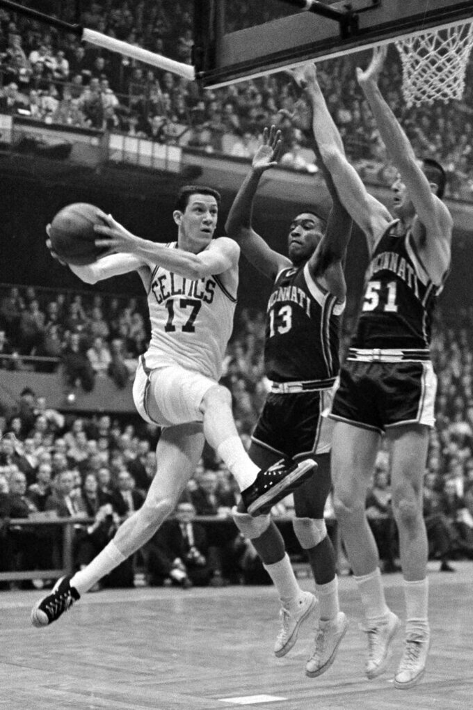 FILE - This March 31, 1963, file photo showing Boston Celtics' John Havlicek going to the basket against Cincinnati Royals Bob Booser (13) and Hub Reed in the fourth period of a semifinal playoff at Boston Garden in Boston. Havlicek, whose steal of Hal Green's inbounds pass in the final seconds of the 1965 Eastern Conference finals against the Philadelphia 76ers remains one of the most famous plays in NBA history, died April 25, 2019. He was 79. (AP Photo/Frank C. Curtin, File)