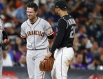 San Francisco Giants pinch-hitter Buster Posey, left, jokes with Colorado Rockies third baseman Nolan Arenado during a pitching change in the eighth inning of a baseball game Saturday, Aug. 3, 2019, in Denver. (AP Photo/David Zalubowski)