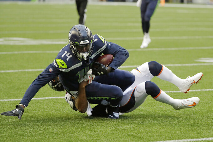 Seattle Seahawks wide receiver DK Metcalf (14) is tackled by Denver Broncos cornerback Chris Harris after making a catch during the first half of an NFL football preseason game Thursday, Aug. 8, 2019, in Seattle. (AP Photo/Elaine Thompson)