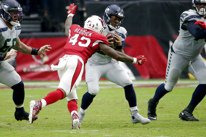 Seattle Seahawks quarterback Russell Wilson (3) is sacked by Arizona Cardinals outside linebacker Haason Reddick (43) pursues during the second half of an NFL football game, Sunday, Sept. 29, 2019, in Glendale, Ariz. (AP Photo/Rick Scuteri)