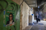 This Friday, Sept. 27, 2019 photo shows election campaign poster of Heba Yazbak, a newly elected Balad party Israeli Arab lawmaker at the market in Nazareth, northern Israel. Electoral gains made by Arab parties in Israel, and their decision to endorse one of the two deadlocked candidates for prime minister, could give them new influence in parliament. But they also face a dilemma dating back to Israel's founding: How to participate in a system that they say relegates them to second-class citizens and oppresses their Palestinian brethren in Gaza and the occupied West Bank. (AP Photo/Oded Balilty)