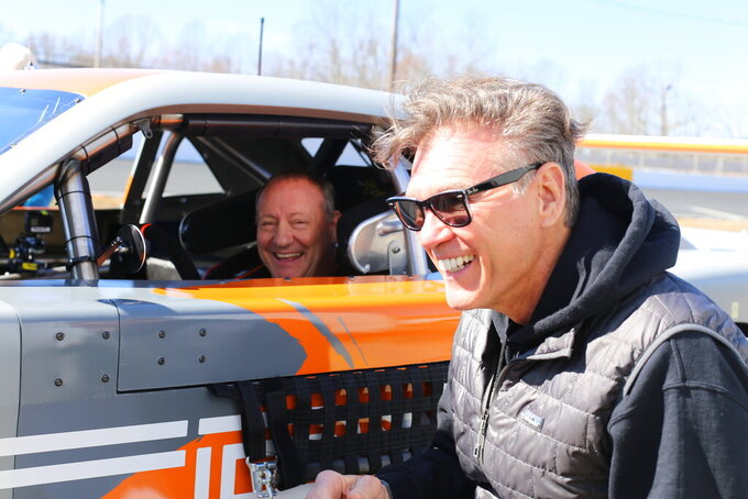 """In this March 8, 2021, photo provided by SRX, Ken Scrader, left, laughs with Ray Evernham during SRX testing at Caraway Speedway in Sophia, N.C. The car will definitely not be the star this summer in the Superstar Racing Experience, which has been formatted for drivers to showcase their skills using what series co-founder Ray Evernham calls """"old-school tools."""" SRX disclosed the format it will use Thursday, May 6, 2021, to The Associated Press when the all-star series launches this summer at Stafford Motor Speedway in Connecticut on June 12 for the first of six Saturday night short-track races across the country. (Garrett Pace/SRX via AP)"""