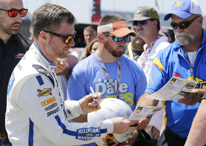 Dale Earnhardt Jr signs autographs before qualifying for the NASCAR Xfinity Series auto race at Darlington Raceway on Saturday, Aug. 31, 2019, in Darlington, S.C.. (AP Photo/Terry Renna)