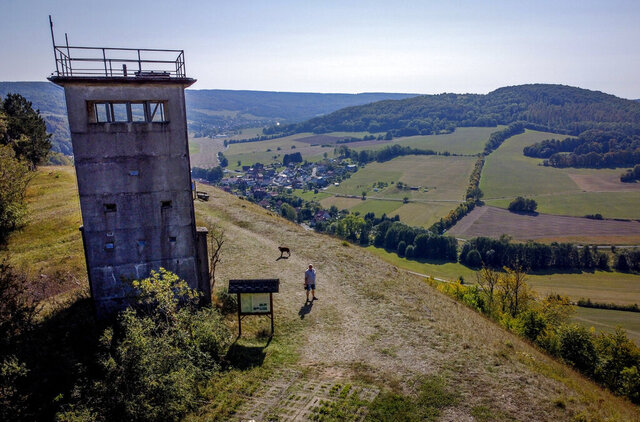 A former East German watch tower stands on a hill high above the former border area between East and West Germany in Unterweid, eastern Germany, Monday, Sept. 21, 2020. Thirty years after Germany was reunited on Oct. 3, 1990, many once-decrepit city centers in the formerly communist east have been painstakingly restored and new factories have sprung up. But many companies and facilities didn't survive the abrupt transition to capitalism inefficient companies found themselves struggling to compete in a market economy, while demand for eastern products slumped and outdated facilities were shut down.  (AP Photo/Michael Probst)