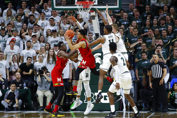 Maryland guard Anthony Cowan Jr. (1) kicks a pass out against Michigan State in the second half of an NCAA college basketball game in East Lansing, Mich., Saturday, Feb. 15, 2020. (AP Photo/Paul Sancya)