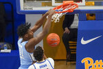 North Carolina's Day'Ron Sharpe (11) dunks in front of Pittsburgh's Terrell Brown during the first half of an NCAA college basketball game Tuesday, Jan. 26, 2021, in Pittsburgh. (AP Photo/Keith Srakocic)