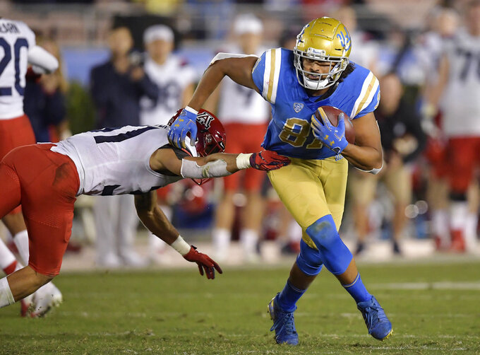 UCLA tight end Caleb Wilson, right, breaks a tackle by Arizona safety Tristan Cooper during the second half of an NCAA college football game Saturday, Oct. 20, 2018, in Pasadena, Calif. UCLA won 31-30. (AP Photo/Mark J. Terrill)
