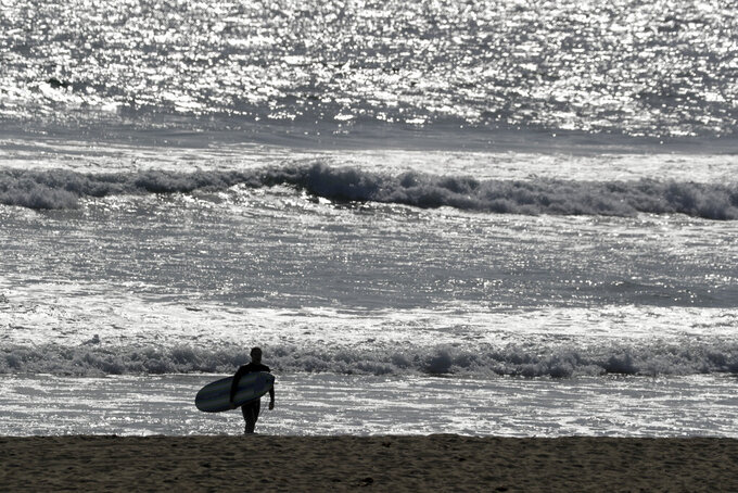 A surfer looks at the water in Huntington Beach, Calif., Saturday, April 4, 2020. With beaches shut down across California as authorities try to stem the spread of the coronavirus, some surfers are simply watching the waves break at home on their TVs. A few are still surfing, seeking out-of-the way breaks or areas where sunbathers are banned from the sand but those carrying boards are tolerated as long as they stay at least six feet apart in the water. (AP Photo/Chris Carlson)