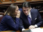 Italian Premier Giuseppe Conte leans to listen to Interior Minister Luciana Lamorgese, left, ahead of confidence vote later, at the Lower Chamber in Rome, Monday, Sept. 9, 2019. Conte is pitching for support in Parliament for his new left-leaning coalition ahead of crucial confidence votes. (AP Photo/Andrew Medichini)
