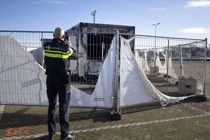 FILE - In this Jan. 24, 2021, file photo, a police officer takes pictures of a burned-out coronavirus testing facility in the fishing village of Urk in the Netherlands after it was set on fire the night before by rioting youths protesting on the first night of a nationwide curfew. A new report by the Geneva-based Insecurity Insight and the University of California, Berkeley's Human Rights Center identified hundreds of attacks linked to fear or frustration around the coronavirus against health care workers and facilities in the past year. (AP Photo/Peter Dejong, File)