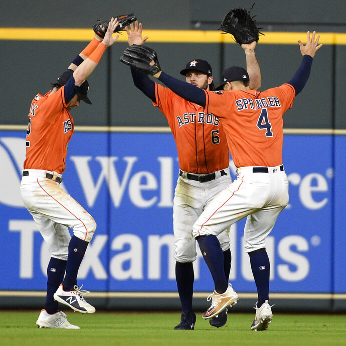 FILE - In this July 6, 2018, file photo, Houston Astros Josh Reddick, left, Jake Marisnick (6), and George Springer do a Fortnite celebration dance after the team's 11-4 win over the Chicago White Sox in a baseball game in Houston. Managers across the league are instituting rules governing gaming, though many say they've left it up to players to decide when to power down the PlayStations.  (AP Photo/Eric Christian Smith)