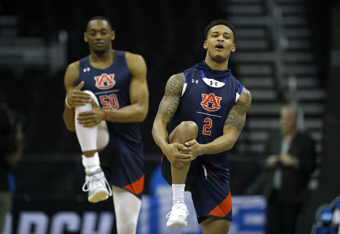 Auburn's Bryce Brown (2) and teammate Austin Wiley (50) warm up during practice at the NCAA men's college basketball tournament Thursday, March 28, 2019, in Kansas City, Mo. Auburn plays North Carolina in a Midwest Regional semifinal on Friday. (AP Photo/Charlie Riedel)