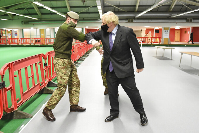 Britain's Prime Minister Boris Johnson elbow bumps a member of the military as he meets troops setting up a vaccination centre in the Castlemilk district of Glasgow, on his one day visit to Scotland, Thursday, Jan. 28, 2021.  Johnson is facing accusations that he is not abiding by lockdown rules as he makes a trip to Scotland on Thursday to laud the rapid rollout of coronavirus vaccines across the United Kingdom. (Jeff Mitchell/Pool Photo via AP)