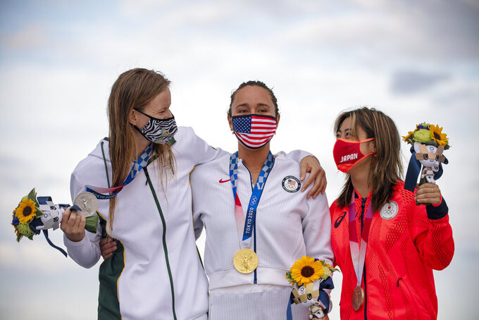 Carissa Moore, center, of the United States, holding her gold medal, South Africa's Bianca Buitendag, left, silver medal and Japan's Amuro Tsuzuki bronze medal celebrate on the podium in the women's surfing competition at the 2020 Summer Olympics, Tuesday, July 27, 2021, at Tsurigasaki beach in Ichinomiya, Japan. (Olivier Morin/Pool Photo via AP)