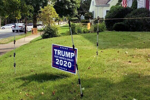 In this September 2020 photo, an electric fence surrounds a campaign sign for President Donald Trump in John Oliveira's yard in New Bedford, Mass. Oliveira said he installed the fence to protect his sign after several were stolen from his lawn during the summer. (John Oliveira via AP)