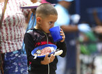 A boy takes a sip of a grape-flavored drink as he holds onto his free lunch at the