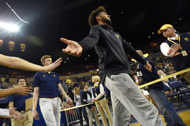 Michigan forward Isaiah Livers, who is injured and not playing, walks onto the court before an NCAA college basketball game against UMass-Lowell, Sunday, Dec. 29, 2019, in Ann Arbor, Mich. (AP Photo/Jose Juarez)