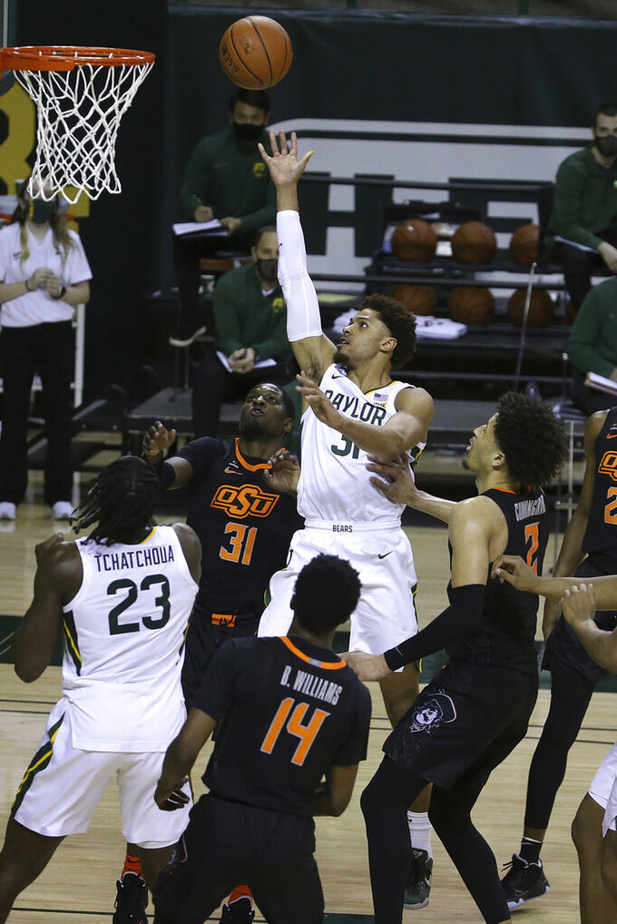Baylor guard MaCio Teague (31) scores against Oklahoma State defenders in the second half of an NCAA college basketball game, Thursday, March 4, 2021, in Waco, Texas. (AP Photo/Jerry Larson)