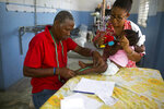 In this May 22, 2019 photo, technician Emmanuel Celicourt measures a child for an orthotic brace at the St. Vincent's Center in Port-au-Prince, Haiti. The workers at St. Vincent's Center were all taught by the 60-year-old technician, who is unable to speak and has been working at the center for decades. (AP Photo/Dieu Nalio Chery)